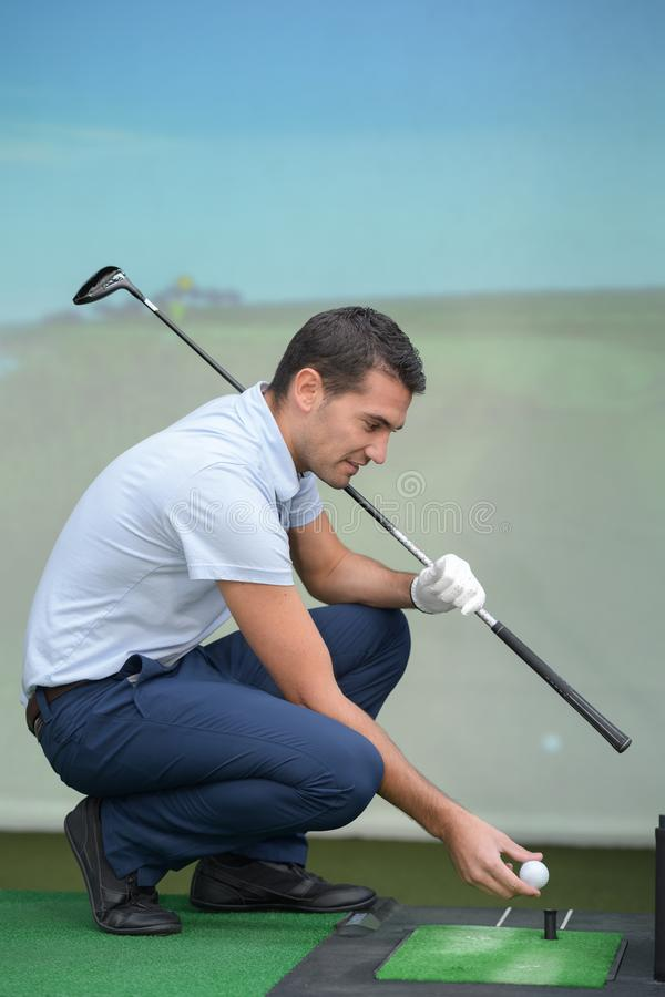 Golfer training in indoor practice royalty free stock photos