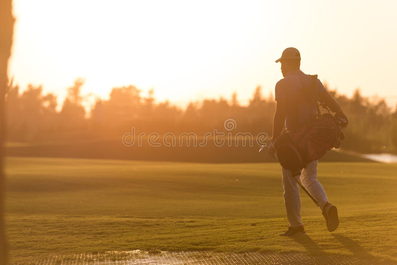 Golfer walking and carrying golf bag at beautiful sunset royalty free stock photo