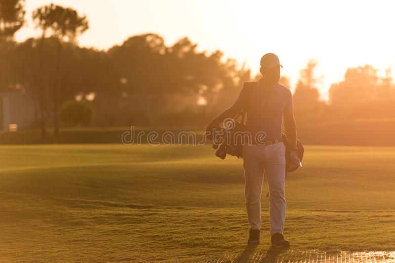 Golfer walking and carrying golf bag at beautiful sunset. Handsome middle eastern golfer carrying bag and walking to next hole at golf course on beautiful sunset stock image