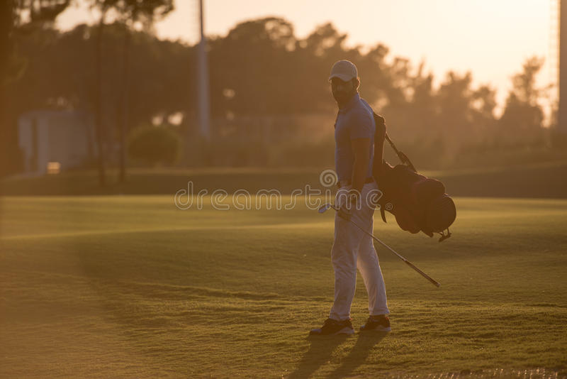 Golfer walking and carrying golf bag at beautiful sunset. Handsome middle eastern golfer carrying bag and walking to next hole at golf course on beautiful sunset stock photography