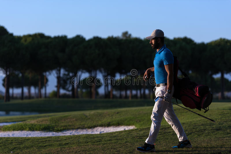 Golfer walking and carrying golf bag at beautiful sunset. Handsome middle eastern golfer carrying bag and walking to next hole at golf course on beautiful sunset royalty free stock photo