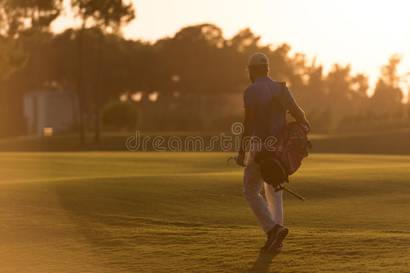 Golfer walking and carrying golf bag at beautiful sunset. Handsome middle eastern golfer carrying bag and walking to next hole at golf course on beautiful sunset stock photos