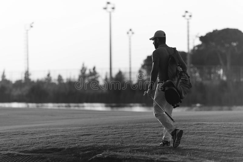 Golfer walking and carrying golf bag at beautiful sunset. Handsome middle eastern golfer carrying bag and walking to next hole at golf course on beautiful sunset royalty free stock image