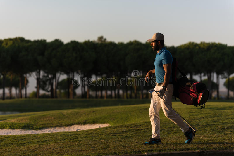 Golfer walking and carrying golf bag at beautiful sunset. Handsome middle eastern golfer carrying bag and walking to next hole at golf course on beautiful sunset royalty free stock photography