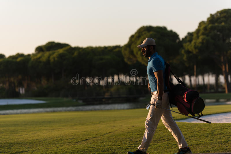 Golfer walking and carrying golf bag at beautiful sunset. Handsome middle eastern golfer carrying bag and walking to next hole at golf course on beautiful sunset royalty free stock photos