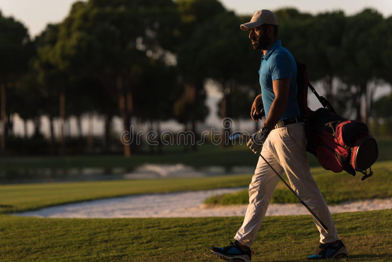Golfer walking and carrying golf bag at beautiful sunset. Handsome middle eastern golfer carrying bag and walking to next hole at golf course on beautiful sunset stock photo