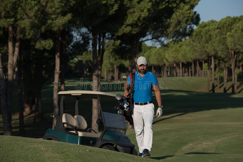 Golfer walking and carrying golf bag. Handsome middle eastern golfer carrying bag and walking to next hole at golf course stock photos