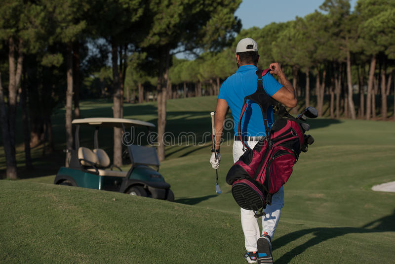 Golfer walking and carrying golf bag. Handsome middle eastern golfer carrying bag and walking to next hole at golf course royalty free stock image