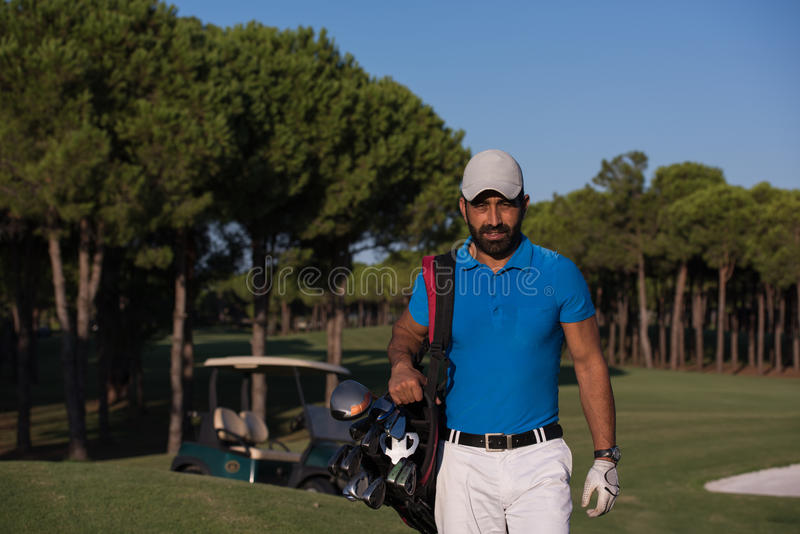 Golfer walking and carrying golf bag. Handsome middle eastern golfer carrying bag and walking to next hole at golf course stock image