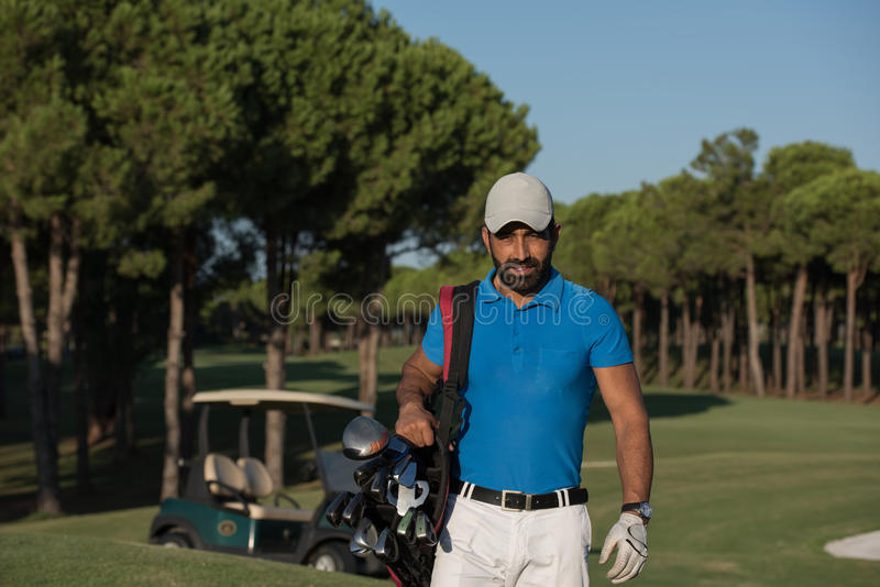 Golfer walking and carrying golf bag. Handsome middle eastern golfer carrying bag and walking to next hole at golf course royalty free stock photos