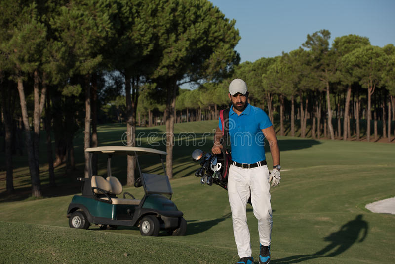 Golfer walking and carrying golf bag. Handsome middle eastern golfer carrying bag and walking to next hole at golf course royalty free stock images