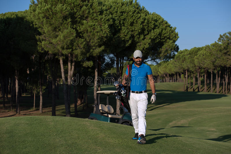 Golfer walking and carrying golf bag. Handsome middle eastern golfer carrying bag and walking to next hole at golf course royalty free stock photography