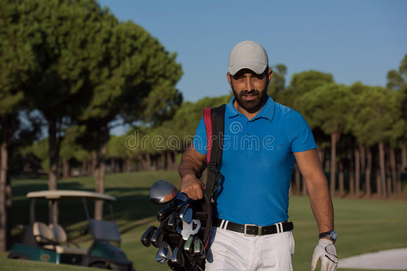 Golfer walking and carrying golf bag. Handsome middle eastern golfer carrying bag and walking to next hole at golf course royalty free stock photo