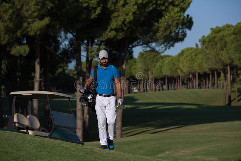 Golfer walking and carrying golf bag. Handsome middle eastern golfer carrying bag and walking to next hole at golf course stock photography