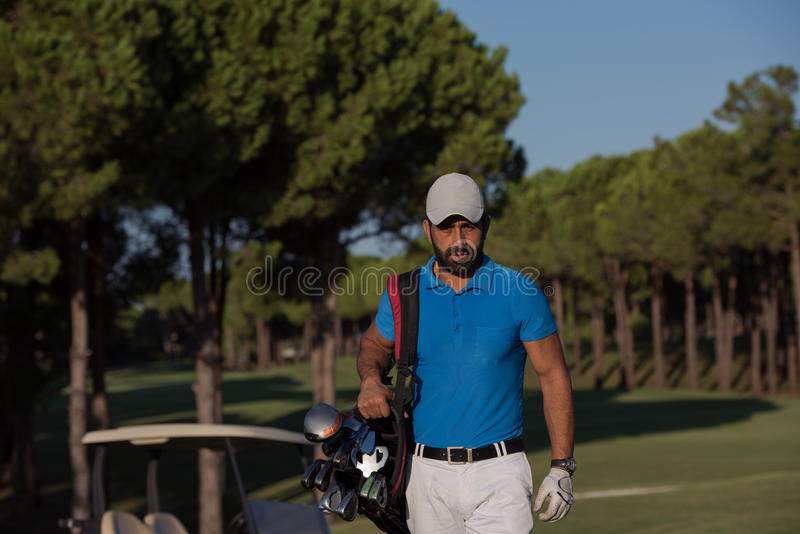 Golfer walking and carrying golf bag. Handsome middle eastern golfer carrying bag and walking to next hole at golf course stock images