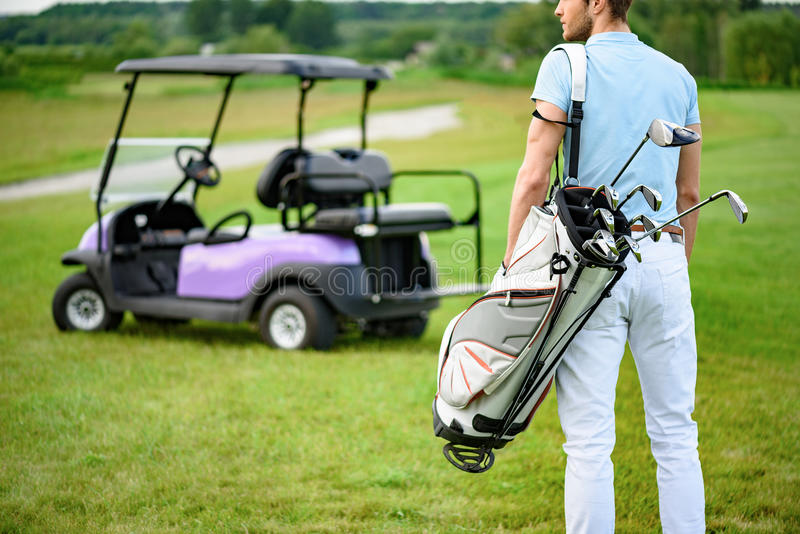 Golfer walking with golf bags stock photography