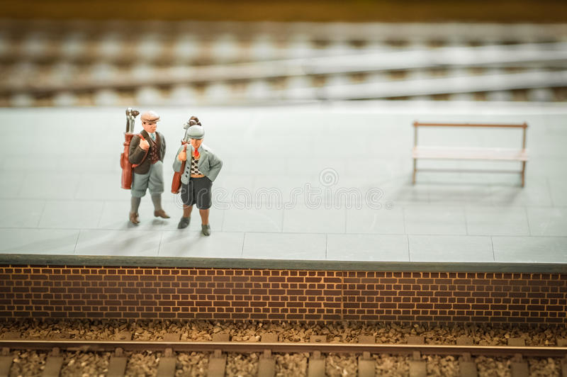 Golfers. Miniature train set figures on a station platform with golf clubs royalty free stock photography