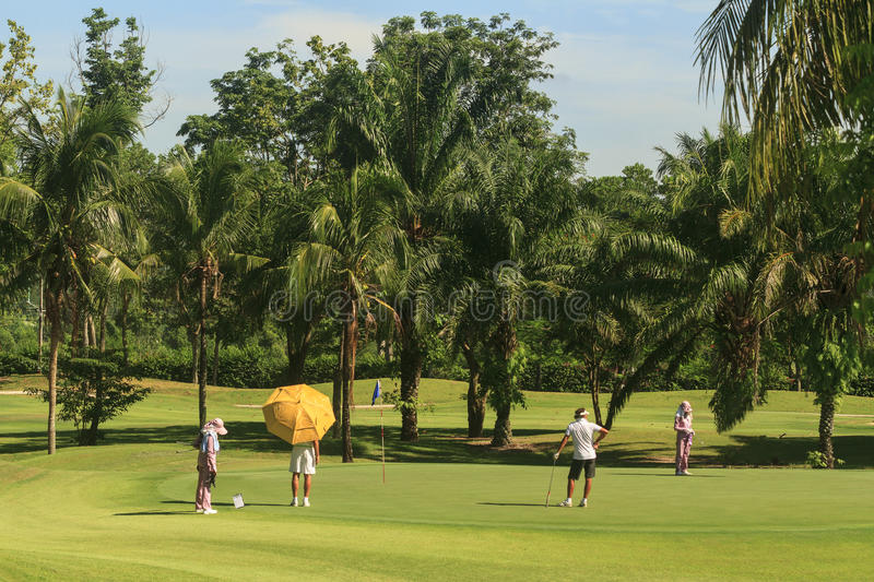 Golfers and caddies on golf course in Thailand stock image