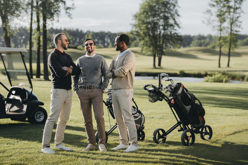 Golfers with golf clubs talking and spending time together on golf course royalty free stock images
