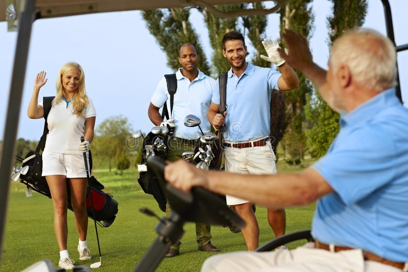Golfers greeting on golf course stock images