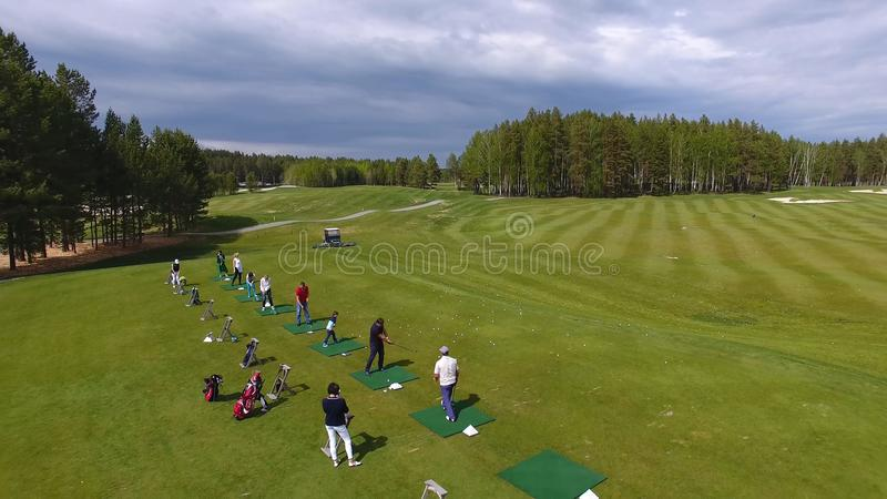 Golfers hitting golf shot with club on course while on summer vacation, aerial stock photos