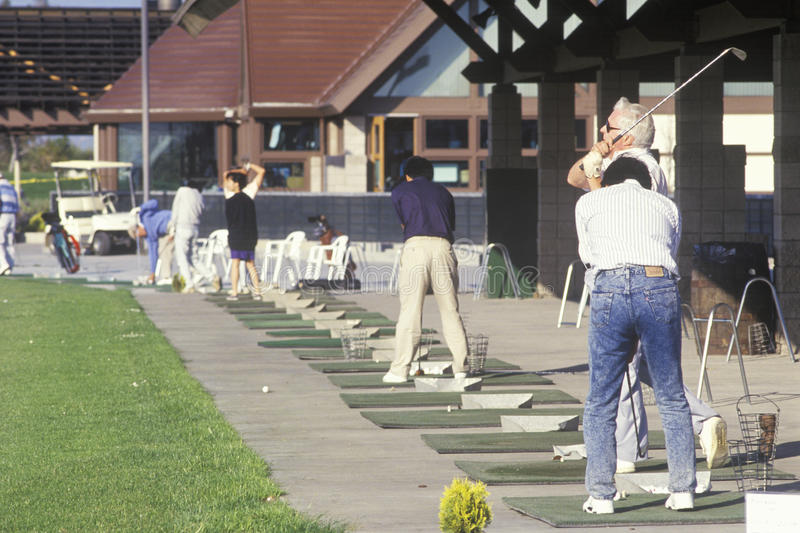 Golfers lined up on putting range,