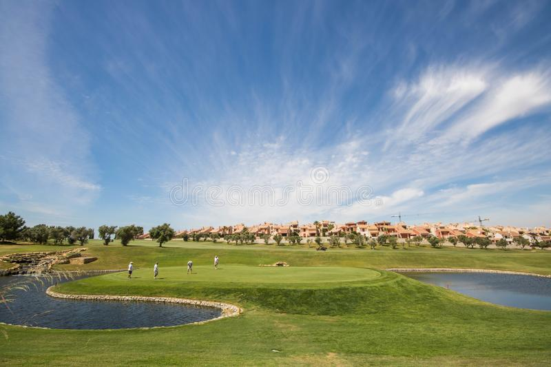 Golfers playing golf in Spain on a perfect summer day. Green surrounded by lakes royalty free stock photos