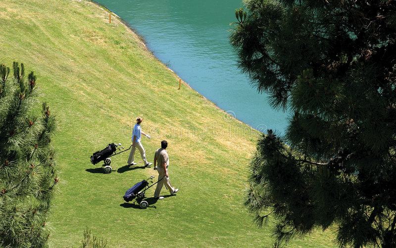 Download Golfers Walking To Their Balls In A Lake. Stock Photo - Image: 123676
