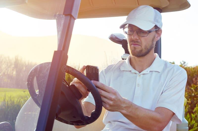 Golfeur à l'aide du téléphone portable APP sur le chariot photographie stock libre de droits