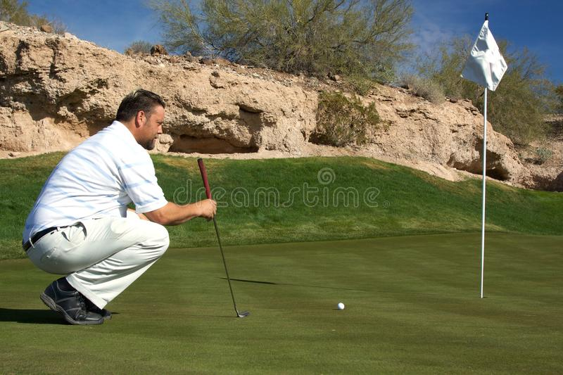 Golfeur alignant un putt photographie stock