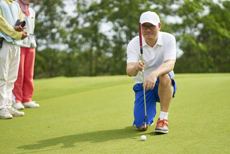 Golfeur asiatique se tapissant dans le terrain de golf visant et se préparant à la mise photo libre de droits