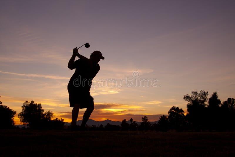 Golfeur au coucher du soleil image stock