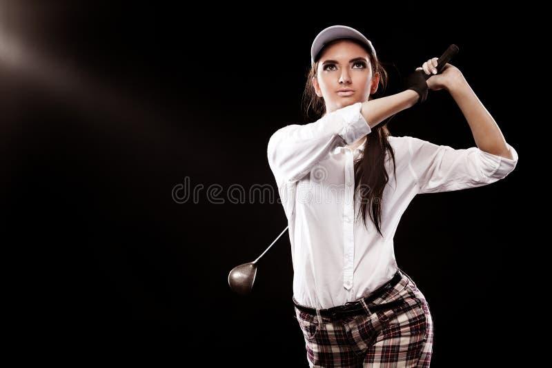 Golfeur de femme frappant la boule d'isolement sur le fond noir Copiez l'espace Concept d'annonce images stock