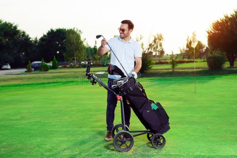 Golfeur de jeune homme sortant le club de golf d'un sac photos libres de droits