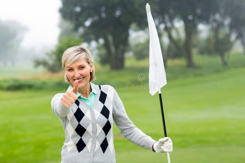 Golfeur de Madame tenant le drapeau photos stock
