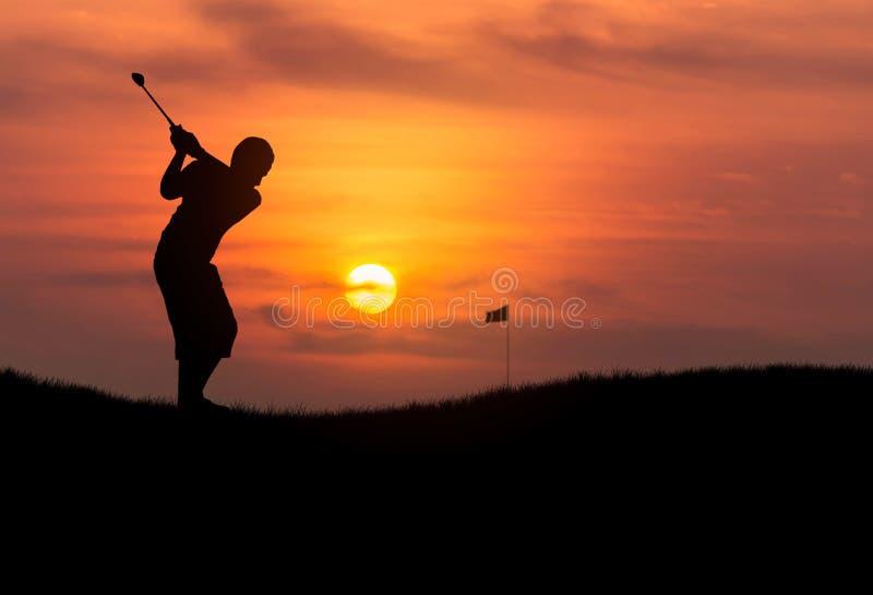 Golfeur de silhouette frappant la boule de golf dans le coucher du soleil image libre de droits