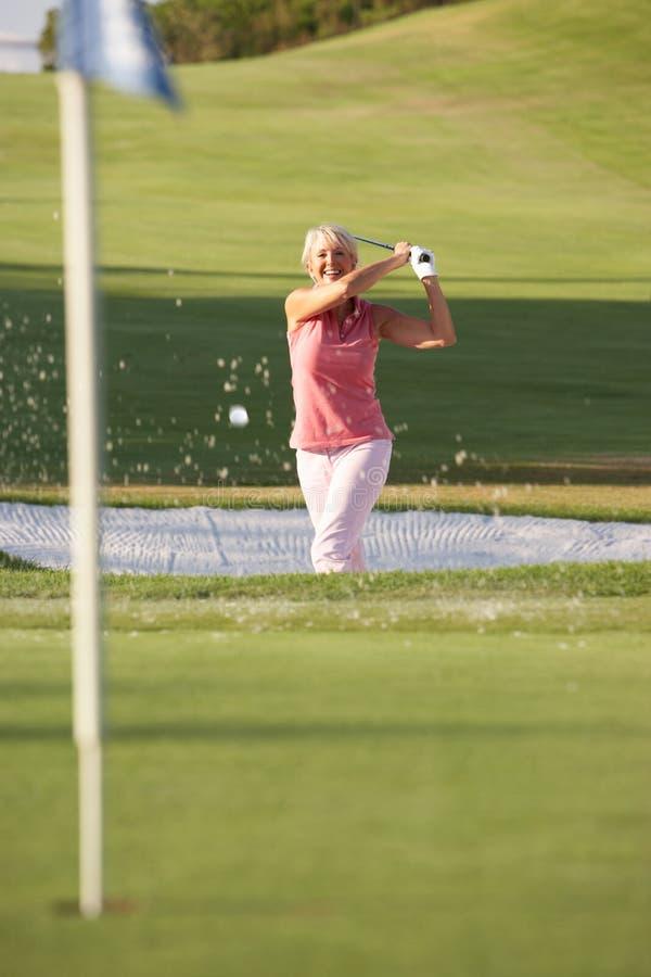 Golfeur féminin aîné jouant le projectile de soute images stock