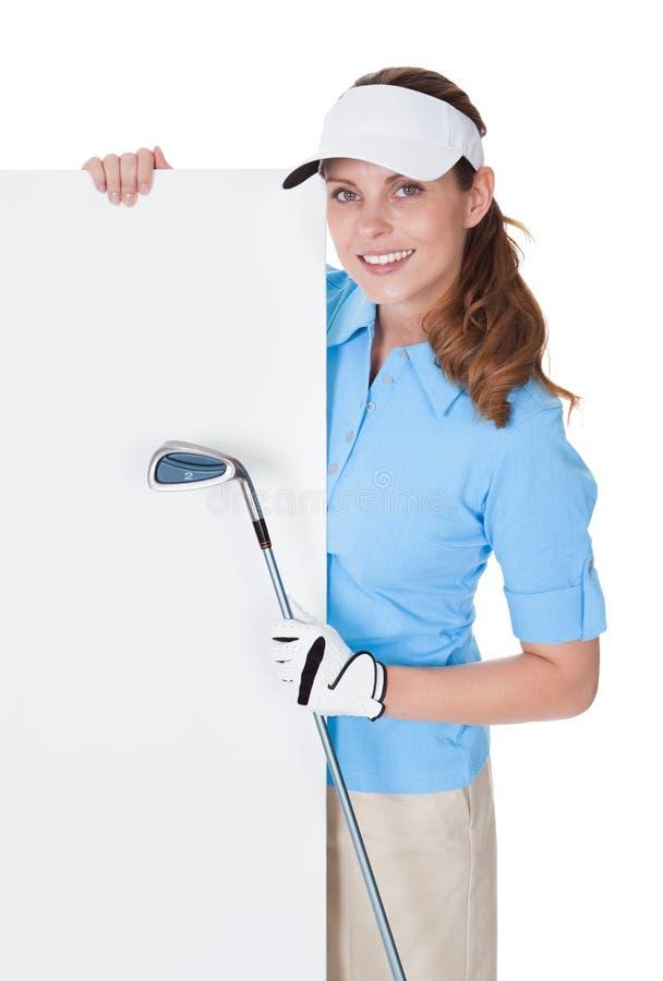 Golfeur féminin avec le panneau blanc photographie stock