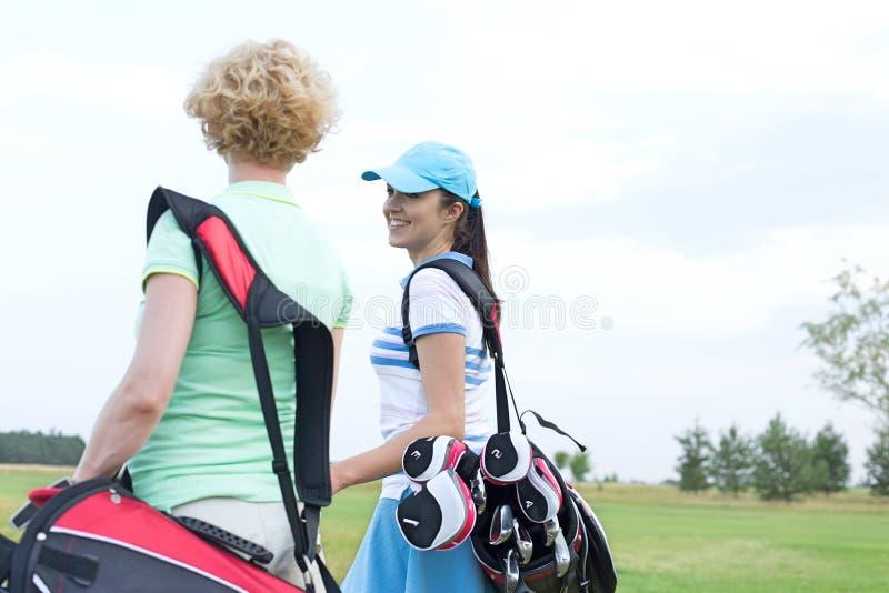 Golfeur féminin de sourire parlant à l'ami au terrain de golf photos libres de droits