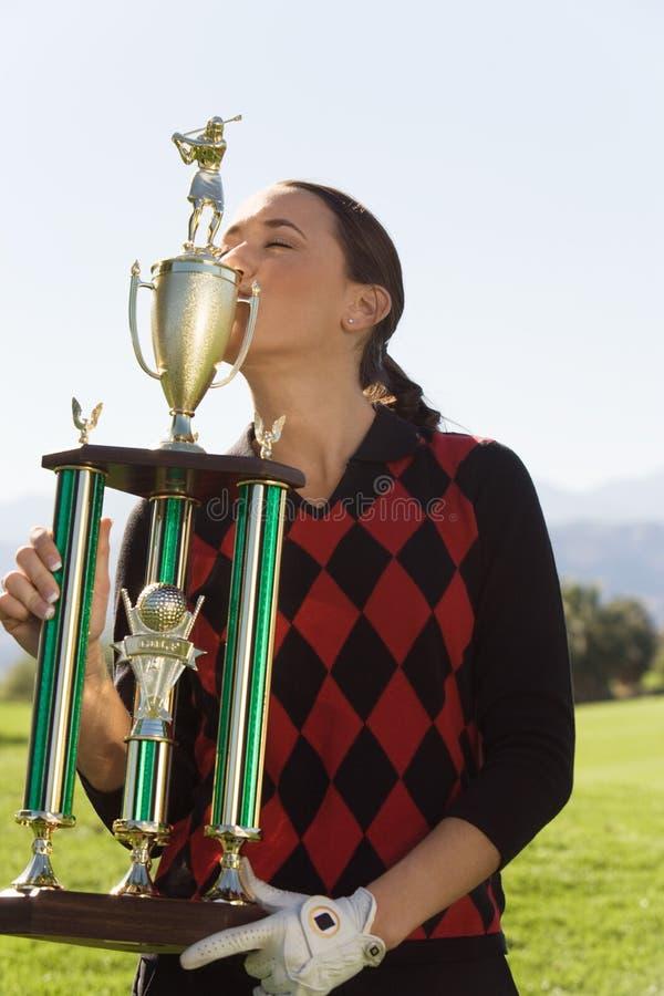 Golfeur féminin embrassant son trophée photos stock