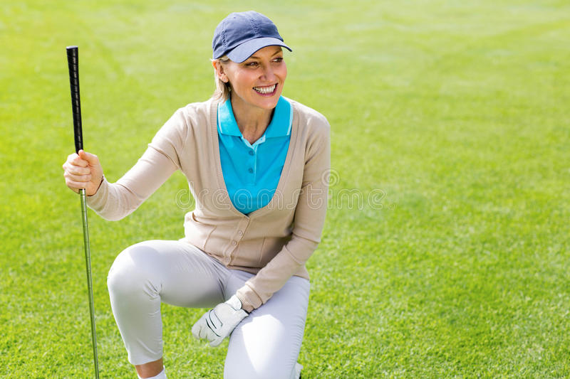 Golfeur féminin kneeing sur le putting green image stock