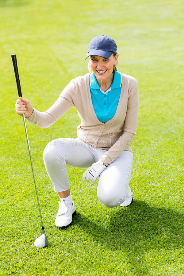 Golfeur féminin kneeing sur le putting green photographie stock