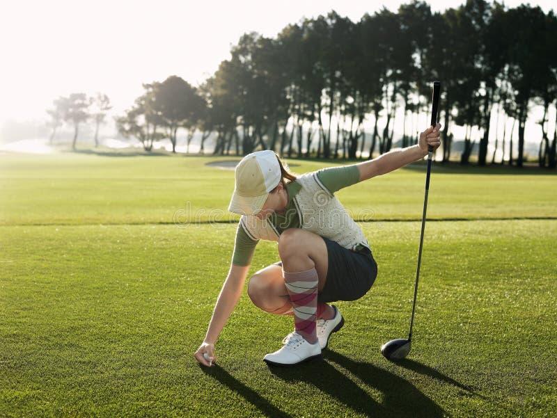 Golfeur féminin plaçant la boule sur la pièce en t image stock