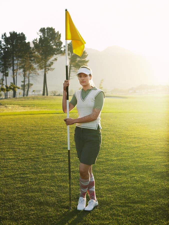 Golfeur féminin tenant le drapeau sur le terrain de golf photos stock