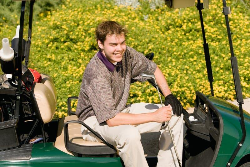 Golfeur masculin détendant dans un chariot de golf photographie stock
