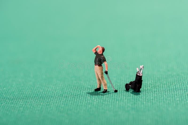 Golfeur miniature scrutant dans la distance photo stock