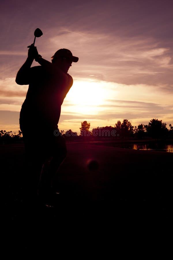 Golfeur piquant hors fonction au coucher du soleil photo stock
