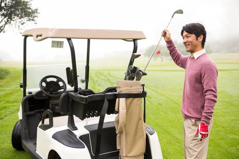 Golfeur prenant le club dans le sac de golf image stock