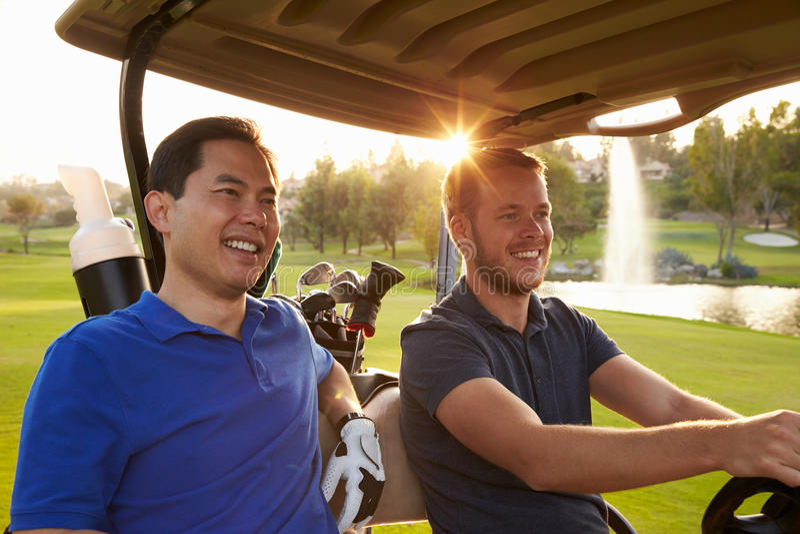 Golfeurs masculins conduisant le boguet le long du fairway du terrain de golf photographie stock
