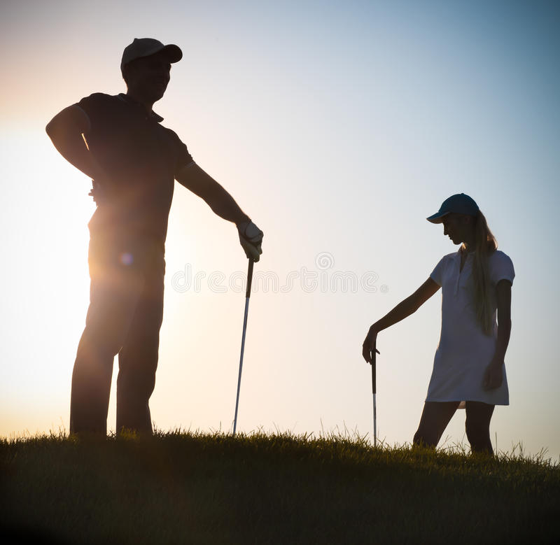 Golfeurs masculins et féminins au coucher du soleil photo libre de droits